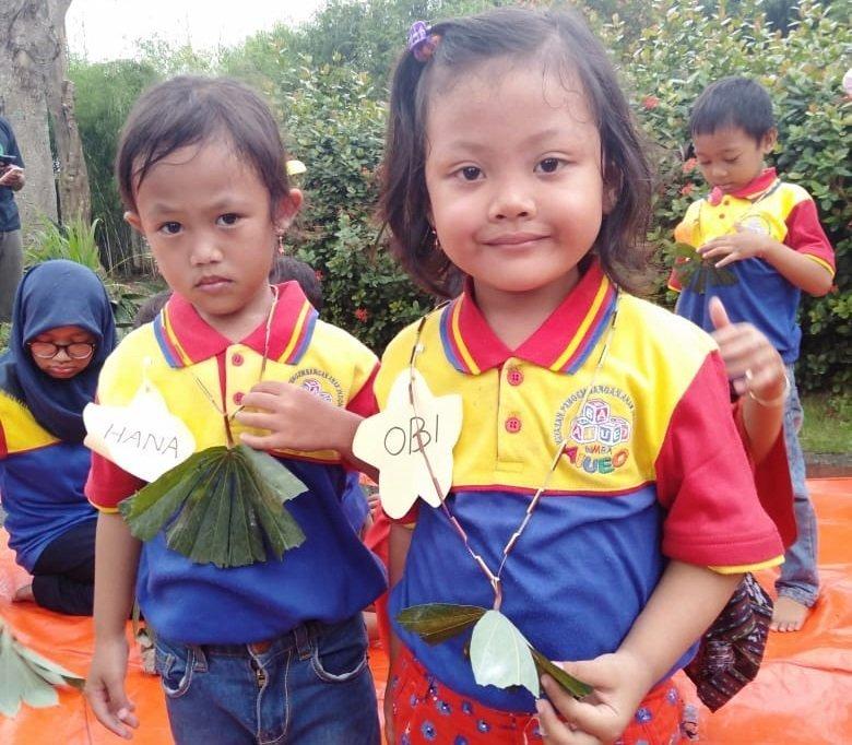 Anak-anak biMBA Buduran membuat kalung dari batang dan daun singkong di taman